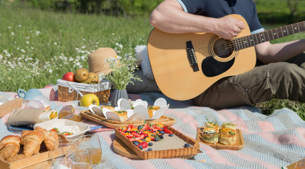 Young people doing picnic and playing guitar in park - Group of happy friends having fun during the weekend outdoor - Friendship, food and drink, funny activities and youth lifestyle concept