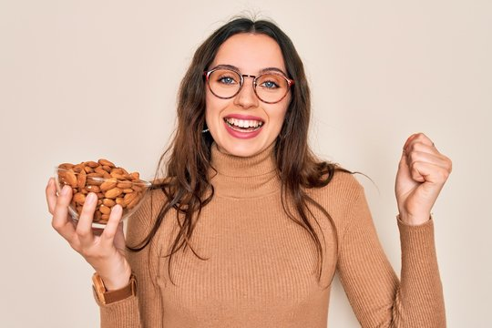 Beautiful woman with blue eyes holding bowl with healthy almonds over white background screaming proud and celebrating victory and success very excited, cheering emotion