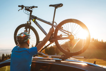 Young Man dresses modern cycling clothes and protective helmet installing his mountain bike on the car roof with sunset backlight. Active sporty people concept image.