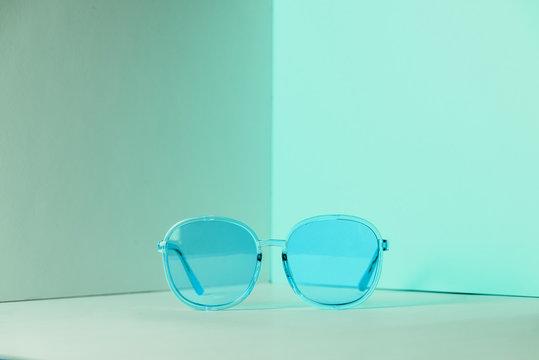 Stylish blue sunglasses on modern minimal pastel background, front view. Nobody. Product photograph