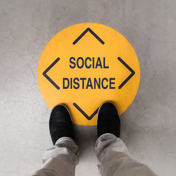 A person standing on a social distancing sign