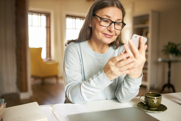 Online communication, aging and retirement concept. Beautiful positive grandmother in eyewear...