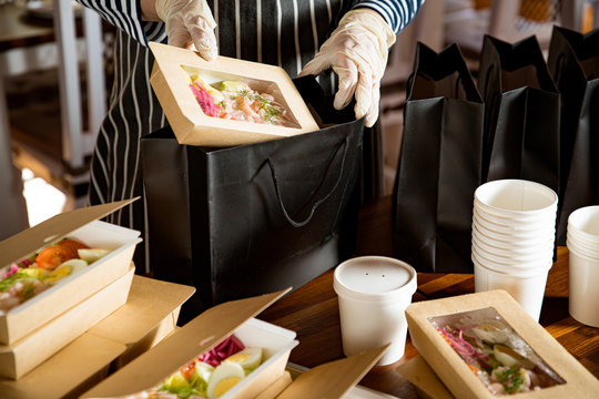 Restaurant worker wearing protective mask and gloves packing food boxed take away. Food delivery services and Online contactless food shopping.