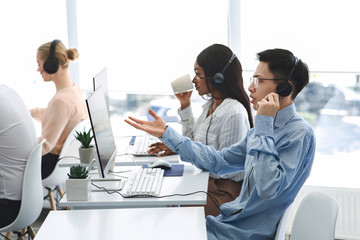Team of customer service agents communicating with clients online at office