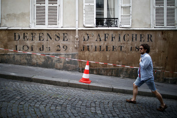 "A resident walks in front of a writing prepared for ""Adieu Monsieur Haffmann"", as the shooting will resume following the outbreak of the coronavirus disease (COVID-19) in Paris"