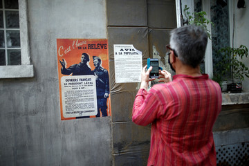 "A person takes a picture of german propaganda and the Vichy government posters edited for ""Adieu Monsieur Haffmann"", as the shooting will resume following the outbreak of the coronavirus disease (COVID-19) in Paris"