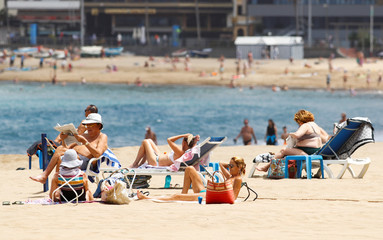 People sunbathe in Las Canteras beach as some Spanish provinces are allowed to ease lockdown restrictions during phase two, on the island of Gran Canaria