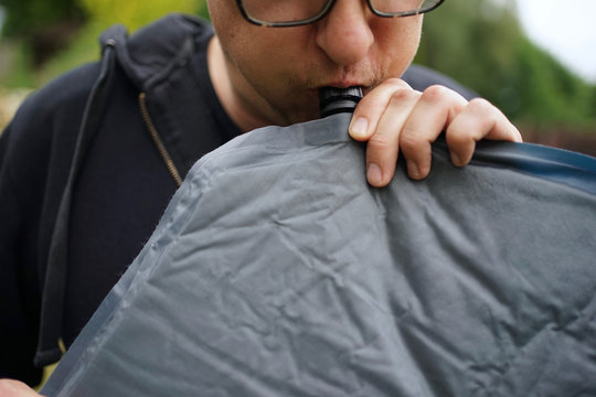 Close up of man with glasses blowing up a self inflatable sleeping pad for camping