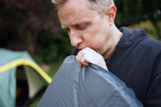 Close up of man blowing up a self inflatable sleeping pad for camping