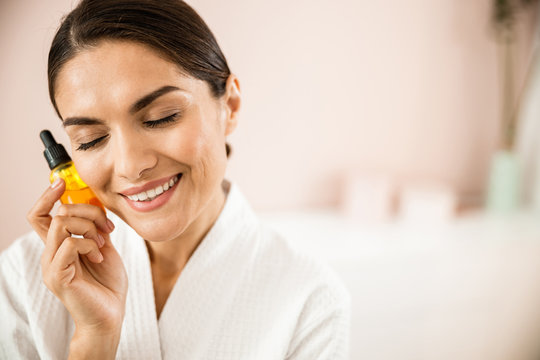 Happy attractive woman with cosmetic drops in hand