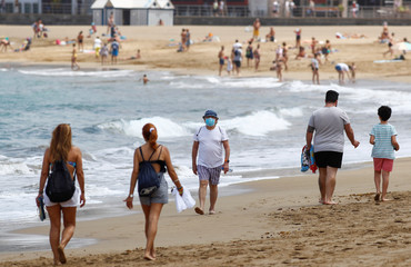 Several people walk along the Las Canteras beach as some Spanish provinces are allowed to ease lockdown restrictions during phase two, on the island of Gran Canaria