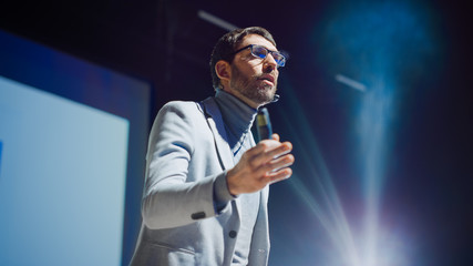 Portrait of Motivational Speaker, Talking about Happiness, Self, Success, Empowerment, Efficiency and How to Be More Productive Self. Large Conference Hall with Cinematographic Light.