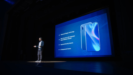 Live Event with Brand New Products Reveal: Speaker Presents Smartphone Device to Audience. Movie Theater Screen Shows Mock-up Touch Screen Mobile Phone with High-Tech Features and Top Highlights