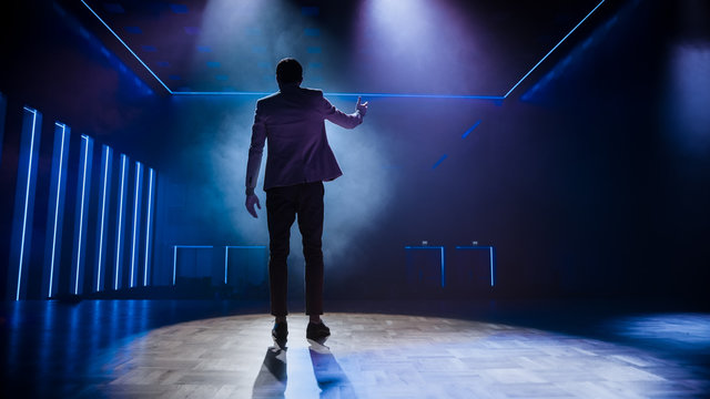 Famous Entertainer Stands on Stage, Greets Audience, Starts Performance. Software Company Founder, Tech Marketing Guru Making a Pitch, Presentation Speaker Giving Talk. Cinematographic Back View