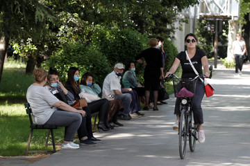 A women rides a bicycle next to people waiting for a bus after Prime Minister Dusko Markovic declared the country the coronavirus disease (COVID-19)-free in Podgorica