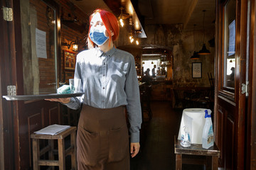 A waitress stands next to disinfectants after Prime Minister Dusko Markovic declared the country the coronavirus disease (COVID-19)-free in Podgorica