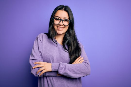 Young brunette woman wearing glasses over purple isolated background happy face smiling with crossed arms looking at the camera. Positive person.