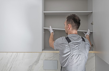 Men Installing Modern Bathroom White Cabinets