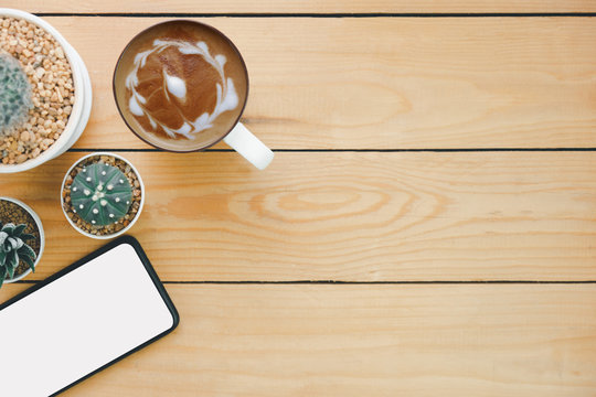 Hot cappuccino art and smart phone and cactus on wooden table, top view, for presentation your product, text on empty space