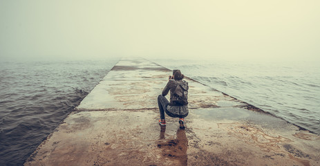 A photographer on a concrete pier takes a picture of a foggy sea.