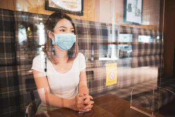Young asian woman wearing surgical mask sitting on table with protection shield against coronavirus outbreak in canteen