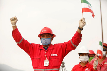 "A worker of the state-oil company Pdvsa holds an Iranian flag during the arrival of the Iranian tanker ship ""Fortune"" at El Palito refinery in Puerto Cabello"