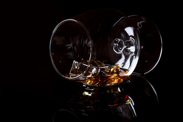 Photo sur Toile Musique Snifter glass with cognac (brandy snifter, brandy bowl, cognac glass, or balloon) lying on a black background with reflection.