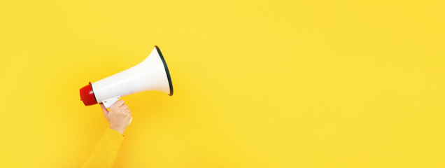 megaphone in hand on a yellow background, attention concept announcement, panoramic mock-up