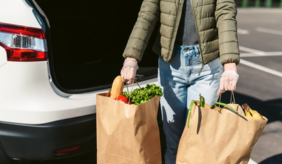 A young woman with grocery bags from a supermarket. Car trunk at background. Social distancing: face mask, disposable gloves to prevent infection. Food shopping during coronavirus Covid 19 epidemic