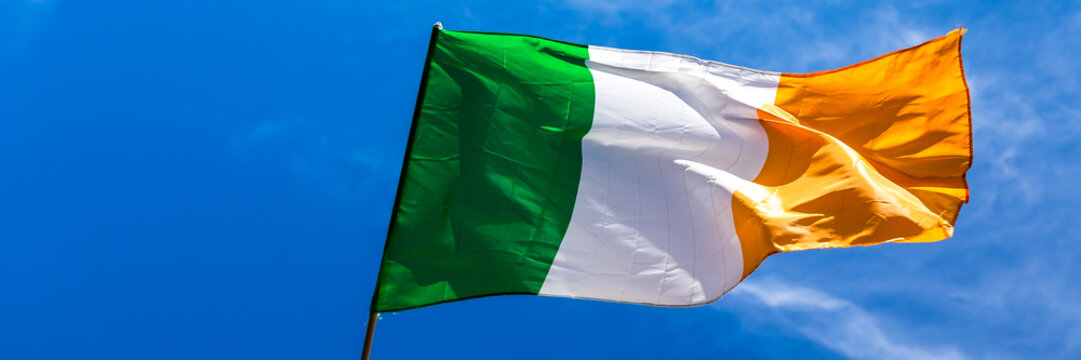 Irish flag fluttering in a brisk breeze against a bright blue sky. Web banner.