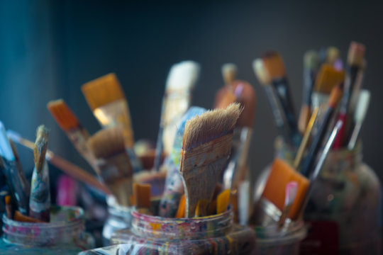 Group of used Colorful Brushes of an Artist in Jars, selective Focus and Copy Space