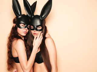 Two sexy beautiful women wearing carnival black mask of Easter bunny rabbit.Hot brunette girls posing near wall in studio. Seductive models in nice lingerie