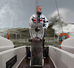 The captain at the wheel of a sailing yacht in storms and very high waves. The man with the beard looks at the rough sea. Large waves roll in from behind and there is spray in the air.