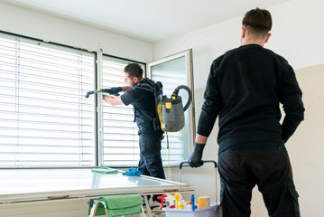A professional cleaning team in an apartment cleaning windows and blinds with a vacuum and other cleaning equipment Wall mural