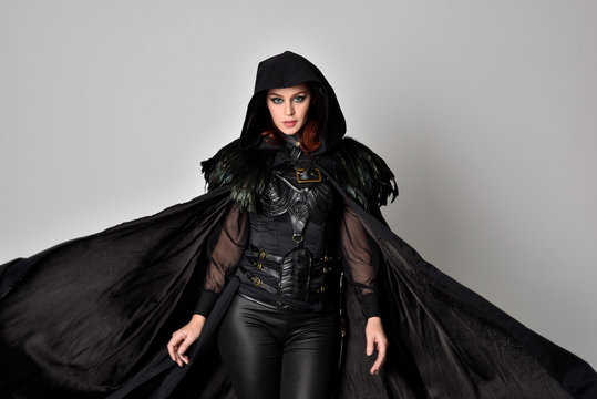 Close up fantasy portrait of a woman with red hair wearing dark leather assassin costume with long black cloak.  isolated against a studio background.