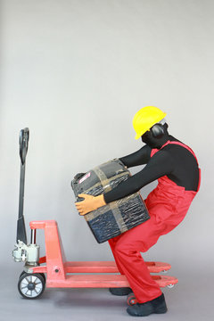 Anonymous worker dealing with heavy package at manual pallet truck.Incorrect body position.Occupational safety and health.