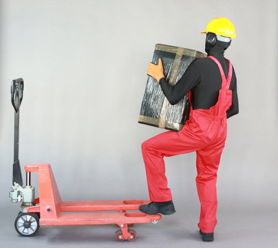 Anonymous worker dealing with heavy package at manual pallet truck.Correct body position.Occupational safety and health.