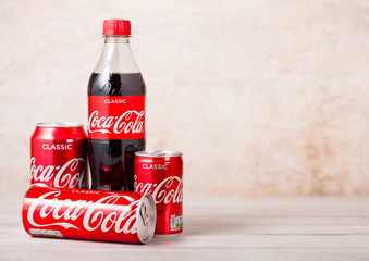 LONDON, UK - AUGUST 03, 2018: Plastic bottle and aluminium tins of Original Coca Cola soft drink on wooden background. Most popular drink in the world.