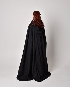 fantasy portrait of a woman wearing long black cloak. Full length standing pose  with back to the camera, isolated against a studio background.