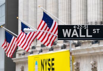 New York, USA - May 14, 2018: Wall Street sign near New York Stock Exchange with flags of the United States. It is the world's most significant financial center.