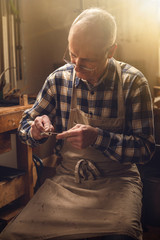 Mature carpenter working on a violin bow