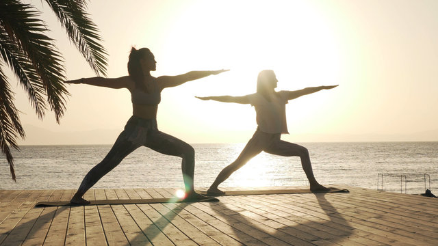 Silhouette of two women practice warrior yoga posture at seaside in sunshine