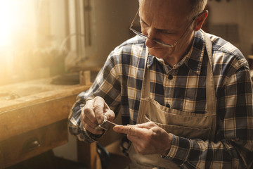 Mature carpenter working on a violin bow with his hands