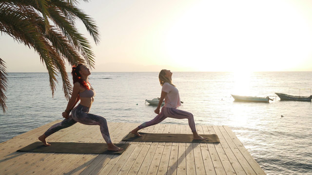 Two women practice warrior yoga posture in seaside pier at sunset