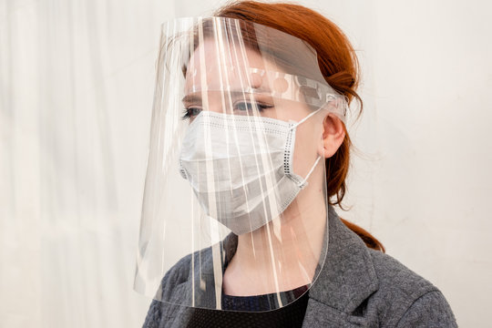 the face of a red-haired girl in a medical mask and protective shield on a white background