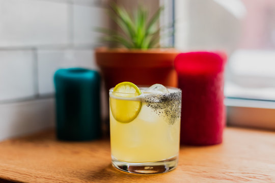 An iced sour cocktail in rocks glass with lemon wheel