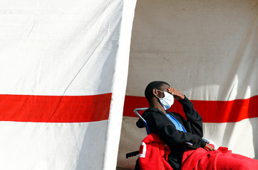 Migrant rescued in the Atlantic Ocean rests in a tent waiting to be transferred by the police, in the port of Arguineguin on the island of Gran Canaria