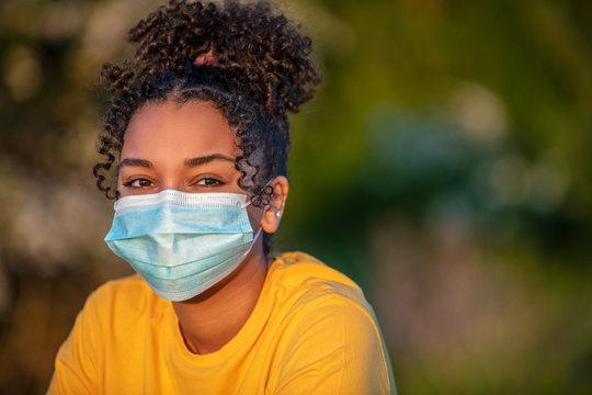 African American Teenager Girl Woman Wearing Coronavirus COVID-19 Face Mask in Virus Pandemic