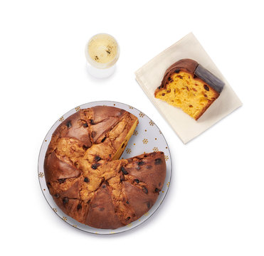 Christmas panettone with cut slice and glass of champagne, isolated on white background, top view