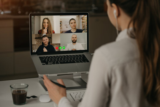 A Back view of a woman working remotely in a video conference with her colleagues during an online meeting. Partners in a video call. Multiethnic business team having a discussion in an online meeting
